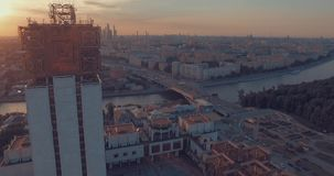 City aerial view at sunset. Aerial view of the Luzhnetsky metro bridge, passenger boat floating along the Moscow River, heavy traffic and building of Russian stock video