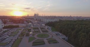 City Aerial View at Sunset. Aerial view of city traffic, busy road near public park, tops of the trees and Moscow River. Top view of modern urban city skyline at stock video footage