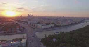 City aerial view at sunset. Aerial view of city traffic, busy road near public park, tops of the trees and Moscow River. Top view of modern urban city skyline at stock footage