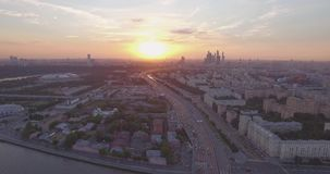 City aerial view at sunset. Aerial view of city traffic, busy road near public park, tops of the trees and Moscow River. Top view of modern urban city skyline at stock video