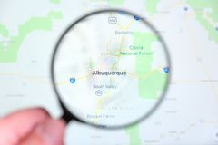 City of Albuquerque, New Mexico on the display screen through a magnifying glass. In a human hand. Selective focus royalty free stock images
