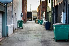 City alley with trash, dumpsters, and garbage cans stock photos