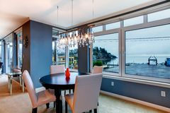 City apartment dining room with round small table and blue walls. Stock Image