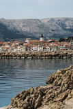City of Baška. Turquoise sea, clean clear water and rocks with old city and mountains in background in Baška, the island of Krk Royalty Free Stock Photo
