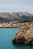 City of Baška. Turquoise sea, clean clear water and rocks with old city and mountains in background in Baška, the island of Krk Royalty Free Stock Images