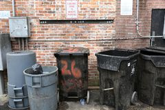 City Back Alley with Garbage Cans Wide Shot. A wide shot of a city back alley behind a pub, showing the tops of garbage cans with a unique brick wall background stock photo