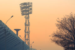 City background silhouette stadium spotlights, bowl for the olympic torch and tree covered with snow at sunset. Stadium Stock Photo