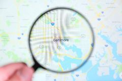 City of Baltimore, Maryland on the display screen. Through a magnifying glass in a human hand royalty free stock images