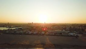 Views from drone during sunset on beach Malvarrosa in Valencia. City, bay and port view during golden hour in beautiful place stock video footage