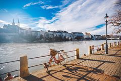 City bicycle with basket on the steering wheel of red color on the quay near the river Rhine in Switzerland against the backdrop o stock photos