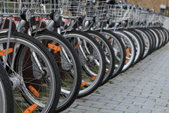 City bicycles. Row of city bicycles parked in a paved street.Selective focus on the first wheel Stock Photo