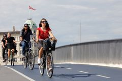 City bicyle riders. Copenhagen, Denmark - August 24, 2017: A group of three cyclists cycles over the bridge Inderhavnbroen Stock Image