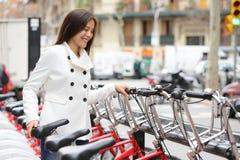 City bike - woman using public city bicycles Stock Image