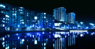 City blue nightline by the water. City blue nightline reflecting from water stock image
