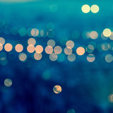 city blurring lights abstract circular bokeh on toned blue background , closeup , retro style stock image
