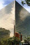 City building. Tall city building made of glass with a reflection of a brick building Royalty Free Stock Photos