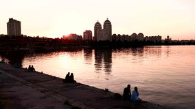 City buildings near water. Couples sitting on embankment. Romantic and quiet place. Clear evening sky stock video