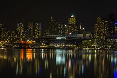 City buildings and stadium lights reflection on water. In Melbourne Docklands Royalty Free Stock Image
