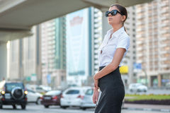City business. Successful arabic businesswoman standing. In the street in formal attire. Businessman standing near skyscrapers in Dubai downtown in sunglasses Royalty Free Stock Images