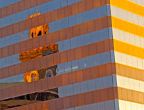 City canvas: Distorted clock tower reflection in the skyscraper wall. Stock Images