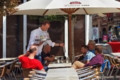 LEUVEN, BELGIUM - SEPTEMBER 05, 2014: Unknown mens are resting in an outdoor cafe in the center of Leuven. stock photography