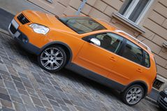 City Car. A city car in striking orange parked on a city side street Stock Image