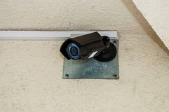 City CCTV camera with blue LEDs. Hanging on a rough house wall royalty free stock photography