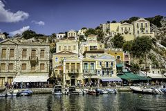 Greek island with pastel colored houses under clear blue skies. City center of the Greek island of Symi with pastel colored houses under clear blue skies, Agean Royalty Free Stock Photography