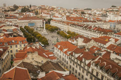 City center, Lisbon, Portugal. A view the city center of Lisbon on a cloudy winter day. The image shows red-tiled roofs of the townhouses and a cloudy sky in Royalty Free Stock Photography