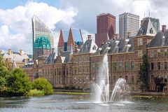 City center view of The Hague in Netherlands. With pond Hofvijver and historical Binnenhof in foreground and modern skyscrapers in bakground royalty free stock photos
