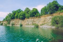 Dolomite quarry and grren water lake. stock photos