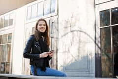 City of chances and fulfilled dreams. Outdoor shot of charming female freelancer sitting near fancy building, holding. Smartphone and looking aside with broad Stock Photo