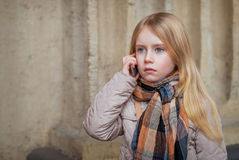 City  child talking on mobile. On the street Stock Images