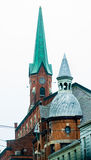 City Church With Green Spires. Older city church with dome and spire and clock faces with brick walls Royalty Free Stock Photography