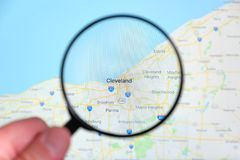 City of Cleveland, Ohio on the display screen through a magnifying glass. In a human hand. Selective focus royalty free stock images