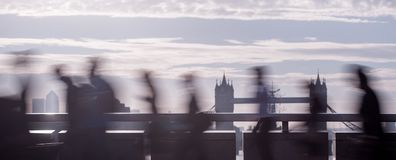 Panoramic - City commuters in London. City commuters. Panoramic intentionally blurred image of workers on London Bridge at sunrise. Unrecognizable faces. London Royalty Free Stock Photos