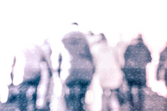 City commuters in winter. Winter city commuters with snow. Blurred image of people walking on the street. back home after work. Defocused figures of people with Royalty Free Stock Image