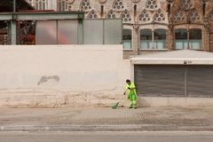 City Council worker. Barcelona, Spain-May 27, 2013 Female council worker sweeping the streets in front of the Sagrada Familia Cathedral, Barcelona, Spain Stock Images