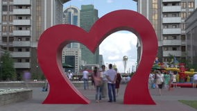 City Day. Time Lapse. Festive city street decorated with a heart symbol. Citizens are photographed near