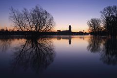 The city of Deventer, The Netherlands, and grassland flooded by the river IJssel. The city of Deventer, The Netherlands, on a cold morning just before sunrise Royalty Free Stock Photos