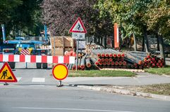 City district heating pipeline reparation and reconstruction parallel with the street with construction machinery and safety road. Traffic barrier around the royalty free stock images