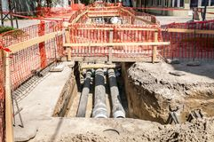 City district heating pipeline reparation and reconstruction parallel with the street with orange construction safety net or barri