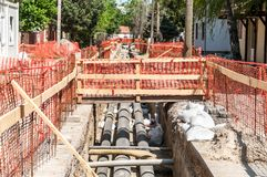 City district heating pipeline reparation and reconstruction parallel with the street with orange construction safety net or barri Royalty Free Stock Photos