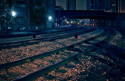 City downtown railway tracks with train bridge at night. Royalty Free Stock Photo