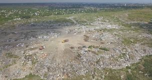 The city dump. City dump in the outskirts of the city near yellow houses. The bulldozer moves along the landfill, leveling out the garbage. Gulls feeding on food stock video