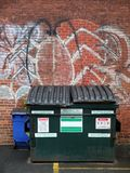 City: dumpster in alley. Dumpster in city alley with graffiti on brick wall Stock Images