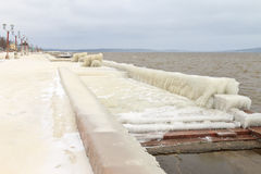 City embankment covered with ice after winter storm on the lake stock photos