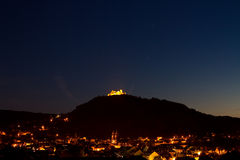 City of Espalion at night. Overview of Espalion at night with the castle Calmont d'Olt in the background royalty free stock photo