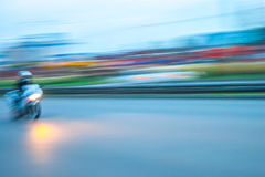 City evening rush hour with a motorcycle rider speeding. Along the street lights on, panning blurry vision Stock Image