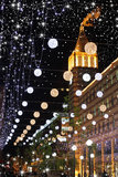 City in expectant of  holiday. Bright nightly boulevard, decorated balls which as if snowflakes as if fall from sky Stock Photo